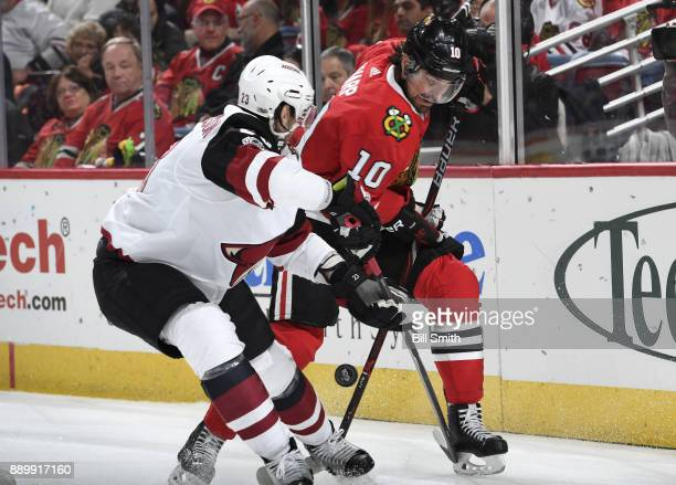 Oliver EkmanLarsson of the Arizona Coyotes and Patrick Sharp of the Chicago Blackhawks battle for the puck in the third period at the United Center...