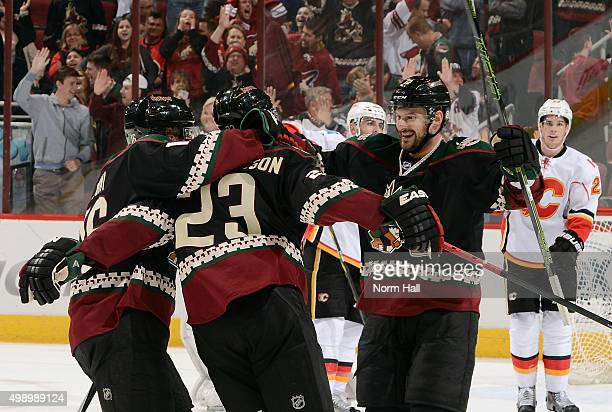 Oliver EkmanLarsson of the Arizona Coyotes celebrates with temmates Max Domi and Brad Richardson after his game winning overtime goal against the...