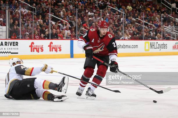 Oliver EkmanLarsson of the Arizona Coyotes moves the puck past PierreEdouard Bellemare of the Vegas Golden Knights during the third period of the NHL...