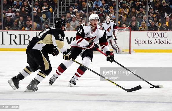 Oliver EkmanLarsson of the Arizona Coyotes moves the puck up ice in front of Kevin Porter of the Pittsburgh Penguins at Consol Energy Center on...