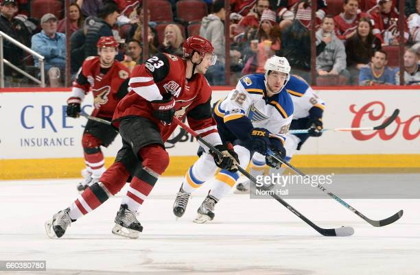 Oliver EkmanLarsson of the Arizona Coyotes skates with the puck in front of Zach Sanford of the St Louis Blues during the third period at Gila River...