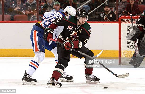 Oliver EkmanLarsson of the Arizona Coyotes skates with the puck while fighting off Jesse Puljujarvi of the Edmonton Oilers during the first period at...
