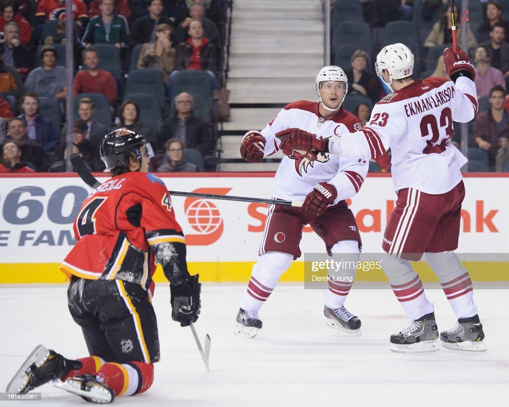 <a gi-track='captionPersonalityLinkClicked' href=/galleries/search?phrase=Oliver+Ekman-Larsson&family=editorial&specificpeople=5894618 ng-click='$event.stopPropagation()'>Oliver Ekman-Larsson</a> #23 of the Phoenix Coyotes celebrates scoring the Coyotes' second goal against the Calgary Flames along with his teammate <a gi-track='captionPersonalityLinkClicked' href=/galleries/search?phrase=Shane+Doan&family=editorial&specificpeople=201614 ng-click='$event.stopPropagation()'>Shane Doan</a> #19 while a dejected <a gi-track='captionPersonalityLinkClicked' href=/galleries/search?phrase=Kris+Russell&family=editorial&specificpeople=879805 ng-click='$event.stopPropagation()'>Kris Russell</a> #4 watches during a preseason NHL game at Scotiabank Saddledome on September 25, 2013 in Calgary, Alberta, Canada.
