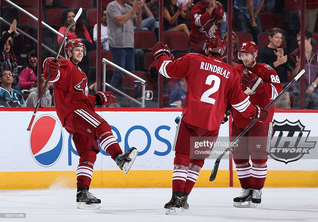 Oliver Ekman-Larsson #23 of the Phoenix Coyotes celebrates with David Rundblad #2 and Mikkel Boedker #89 after Ekman-Larsson scored a third period goal against the San Jose Sharks during the preseason NHL game at Jobing.com Arena on September 27, 2013 in Glendale, Arizona.