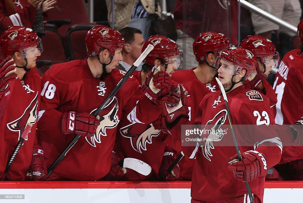 Oliver Ekman-Larsson #23 of the Phoenix Coyotes celebrates with teammates on the bench after scoring a third period goal against the San Jose Sharks during the preseason NHL game at Jobing.com Arena on September 27, 2013 in Glendale, Arizona.