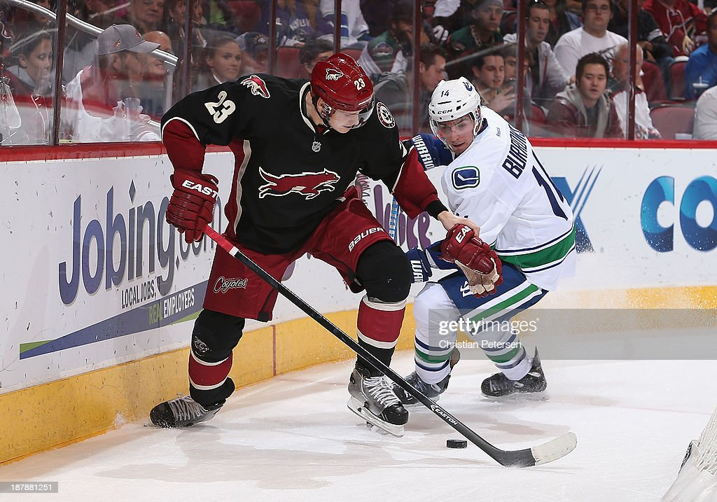 <a gi-track='captionPersonalityLinkClicked' href=/galleries/search?phrase=Oliver+Ekman-Larsson&family=editorial&specificpeople=5894618 ng-click='$event.stopPropagation()'>Oliver Ekman-Larsson</a> #23 of the Phoenix Coyotes handles the puck against Alex Burrows #14 of the Vancouver Canucks during the NHL game at Jobing.com Arena on November 5, 2013 in Glendale, Arizona. The Coyotes defeated the Canucks 3-2 in an overtime shoot out.