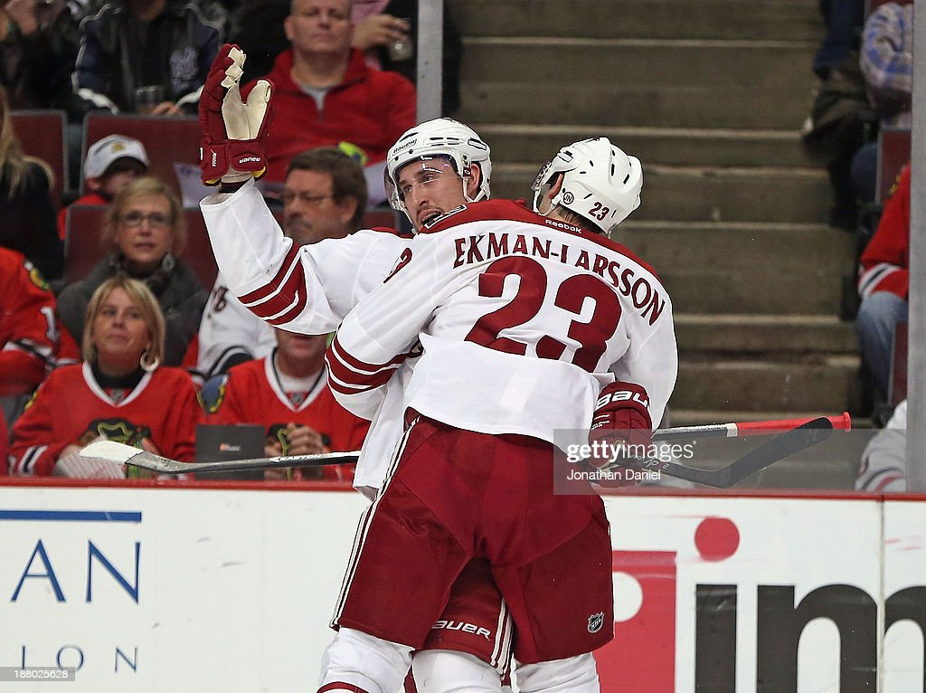 Oliver Ekman-Larsson #23 of the Phoenix Coyotes hugs teammate Michael Stone after Stone's second period goal against the Chicago Blackhawks at the United Center on November 14, 2013 in Chicago, Illinois.