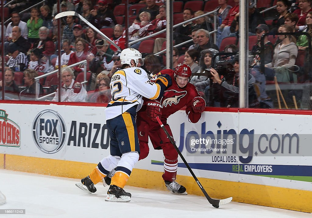 Oliver Ekman-Larsson #23 of the Phoenix Coyotes is checked by Mike Fisher #12 of the Nashville Predators during the second period of the NHL game at Jobing.com Arena on October 31, 2013 in Glendale, Arizona.