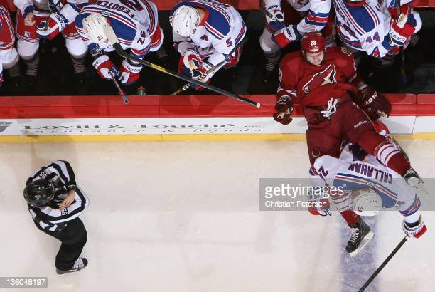 Oliver EkmanLarsson of the Phoenix Coyotes is checked onto the bench by Ryan Callahan of the New York Rangers during the NHL game at Jobingcom Arena...