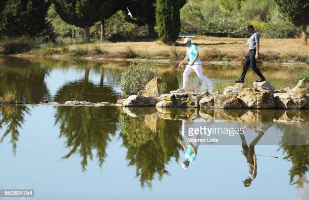 Oliver Fisher of England and Thomas Pieters of Belgium cross to the 17th tee during day four of the Portugal Masters at Dom Pedro Victoria Golf Club...