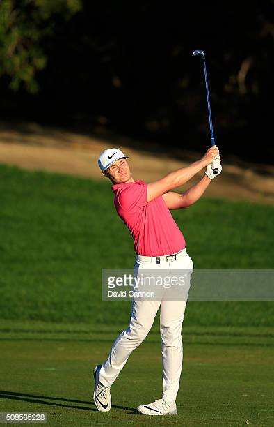 Oliver Fisher of England plays his second shot at the par 4 ninth hole during the second round of the 2016 Omega Dubai Desert Classic on the Majlis...