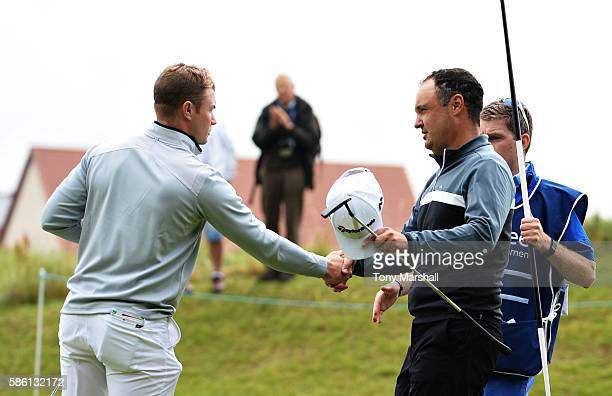 Oliver Fisher of England shakes hands with Simon Khan of England after winning their match on hole 17 on day two of the Aberdeen Asset Management...