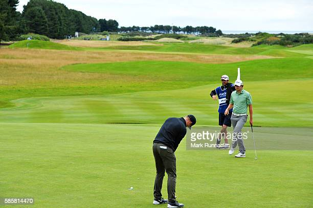 Oliver Fisher of England takes a putt on hole 18 opponent Peter Uihlein of United States looks on on day one of the Aberdeen Asset Management Paul...