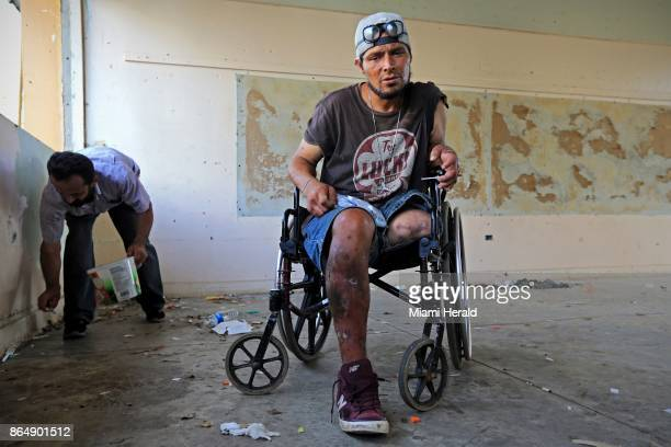 Oliver Franco Rivero holds a new syringe before injecting himself with heroine and cocaine at an abandoned school in Cidra Puerto Rico on October 19...