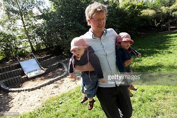 Oliver H a married federal employee on 6month paternity leave plays with his twin 14monthold daughters Lotte and Alma at a playground near his home...