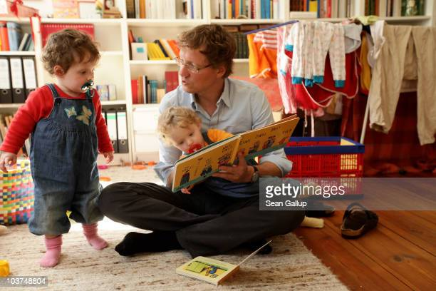 Oliver H a married federal employee on 6month paternity leave reads to his twin 14monthold daughters Alma and Lotte at his home on August 31 2010 in...