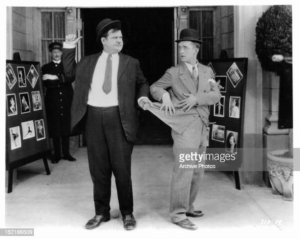 Oliver Hardy pulling on the coat of Stan Laurel in a scene from the short 'Their Purple Moment' 1928