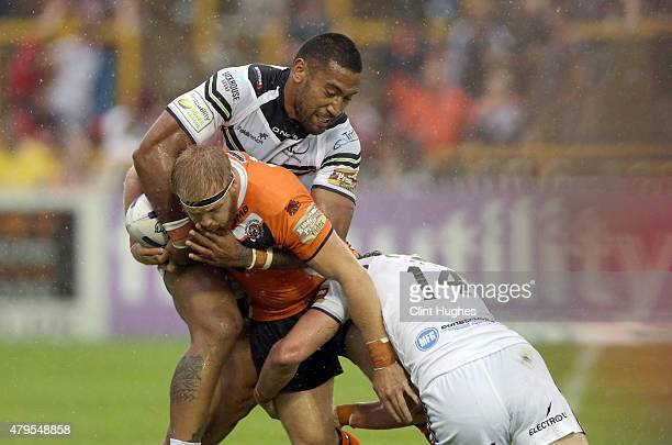 Oliver Holmes of Castleford Tigers is tackled by Manase Manuokafoa and Chris Dean of Widnes Vikings during the First Utility Super League match...