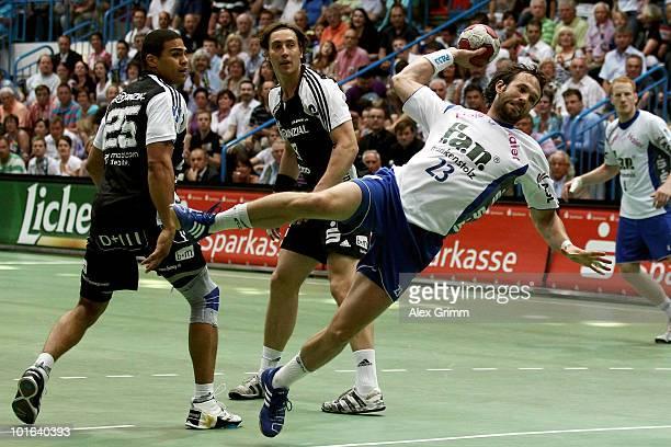 Oliver Koehrmann of Grosswallstadt is challenged by Hendrik Pekeler and Daniel Narcisse of Kiel during the Toyota Handball Bundesliga match between...