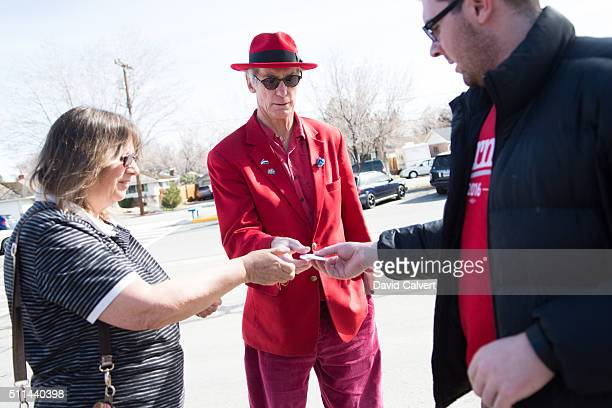 Oliver Larkin a staffer from Sen Bernie Sanders' campaign passes out buttons to supporters Kathy Rusco and Joe Tyler outside Swope Middle School...
