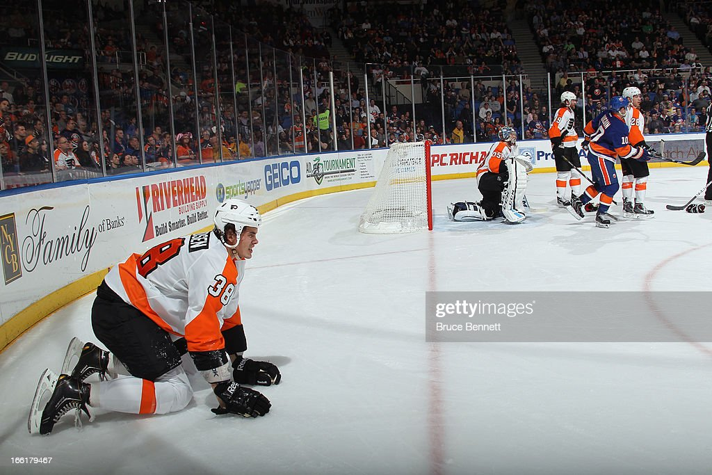 Oliver Lauridsen #38 of the Philadelphia Flyers kneels on the ice after being hit by Michael Grabner #40 of the New York Islanders during the second period at the Nassau Veterans Memorial Coliseum on April 9, 2013 in Uniondale, New York.