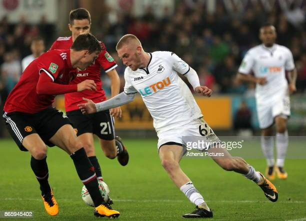 Oliver McBurnie of Swansea City attempts to run past two Manchester United players during the Carabao Cup Fourth Round match between Swansea City and...