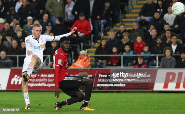 Oliver McBurnie of Swansea City has a shot on goal under whilst pressure from Axel Tuanzebe of Manchester United during the Carabao Cup Fourth Round...