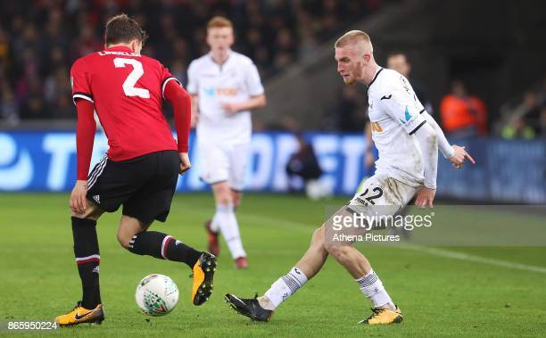 Oliver McBurnie of Swansea City is marked by Victor Lindelof of Manchester United during the Carabao Cup Fourth Round match between Swansea City and...