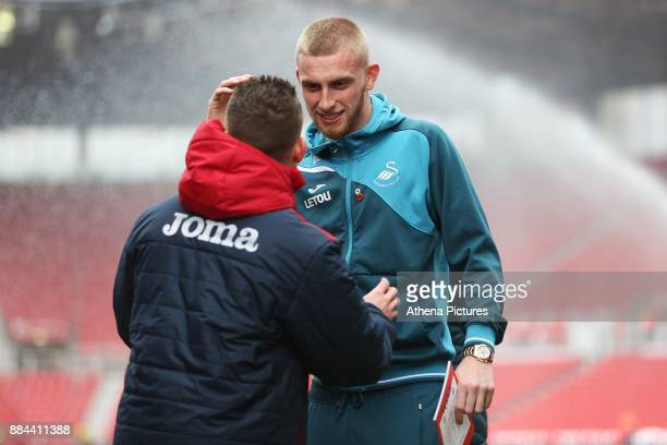 Oliver McBurnie of Swansea City talks to a backroom member of Staff as he arrives at the bet365 Stadium prior to kick off of the Premier League match...