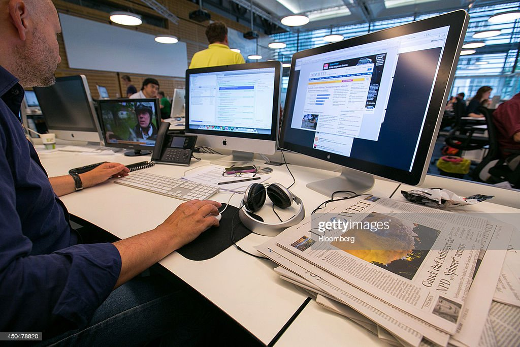 Oliver Michalsky, deputy editor-in-chief of Die Welt newspaper, sits at a desktop computer as he works on an online edition of the broadsheet newspaper, inside the offices of publisher Axel Springer SE in Berlin, Germany, on Wednesday, June 11, 2014. Axel Springer SE, Europe's biggest newspaper publisher, is working with JPMorgan Chase & Co. and Citigroup Inc. on an initial public offering of its digital-classifieds business, people familiar with the matter said. Photographer: Krisztian Bocsi/Bloomberg via Getty Images