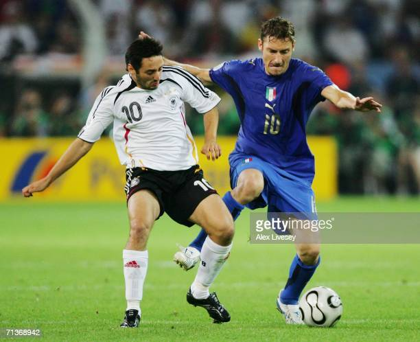 Oliver Neuville of Germany battles for the ball with Francesco Totti of Italy during the FIFA World Cup Germany 2006 Semifinal match between Germany...