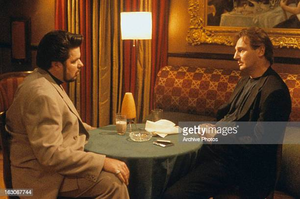 Oliver Platt sits down with Liam Neeson in a scene from the film 'Gun Shy' 2000