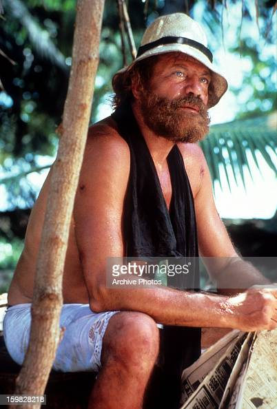Oliver Reed holds a paper in a scene from the film 'Castaway' 1986