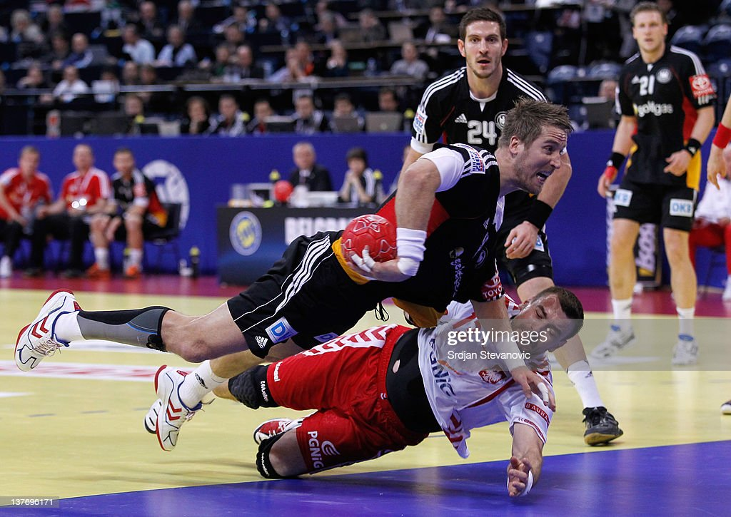 Oliver Roggisch (top) of Germany competes with Bartosz Jurecki (below) of Poland during the Men's European Handball Championship 2012 second round group one, match between Poland and Germany at Arena Hall on January 25, 2012 in Belgrade, Serbia.