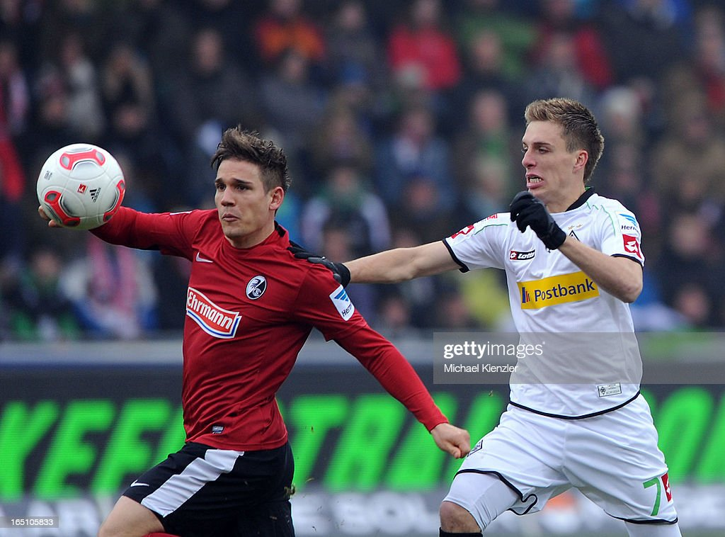 Oliver Sorg of Freiburg (L) challenges Patrick Herrmann of VfL Borussia Moenchengladbach during the Bundesliga match between SC Freiburg and VfL Borussia Moenchengladbach at MAGE SOLAR Stadium on March 30, 2013 in Freiburg, Germany.