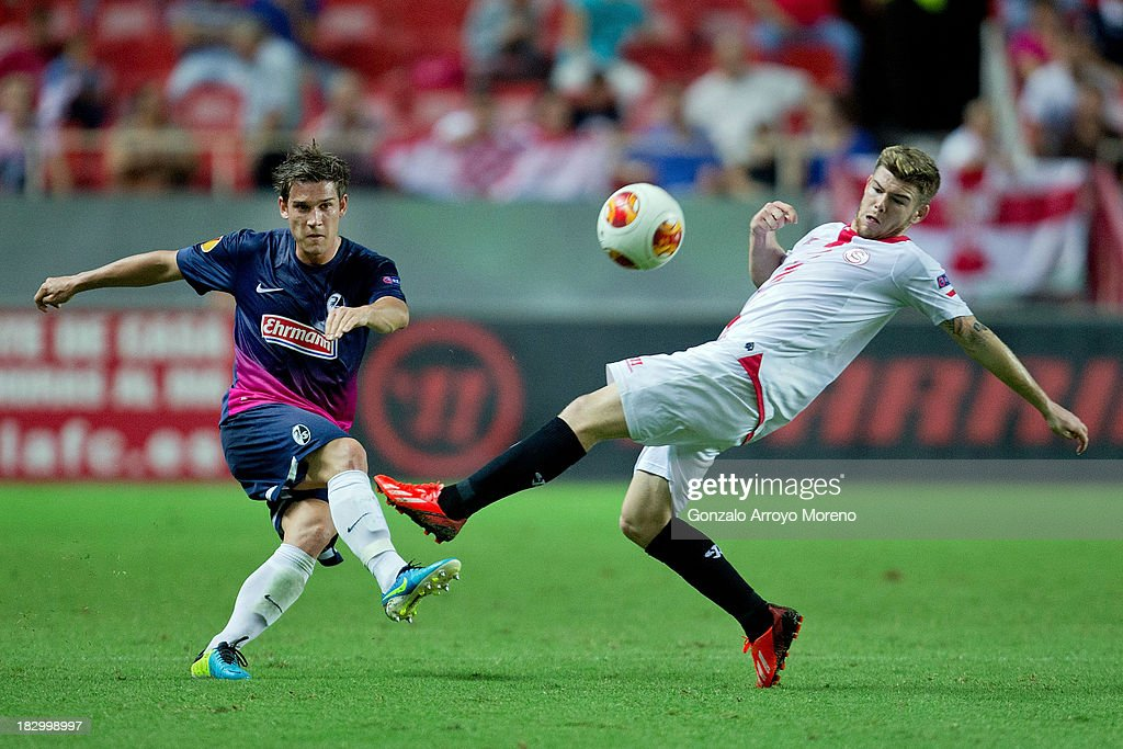 Oliver Sorg (L) of SC Freiburg competes for the ball with Alberto Moreno (R) of Sevilla FC during the UEFA Europa League group H match between Sevilla FC and SC Freiburg at Estadio Ramon Sanchez Pizjuan on October 3, 2013 in Seville, Spain.