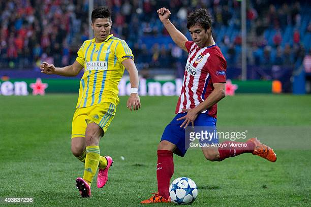 Oliver Torres of Atletico de Madrid competes for the ball with Georgi Zhukov of FC Astana during the UEFA Champions League Group C match between Club...