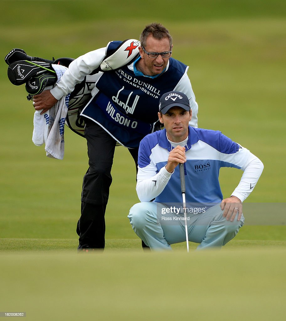Oliver Wilson of England lines up his putt with his caddy on the 17th green during the second round of the Alfred Dunhill Links Championship on The Old Course, at St Andrews on September 27, 2013 in St Andrews, Scotland.