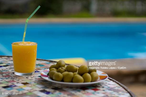 Olives And Glass Of Juice Served On Table Against Swimming Pool