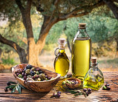 Olives and olive oil in a bottle on the background of the evening olive grove.