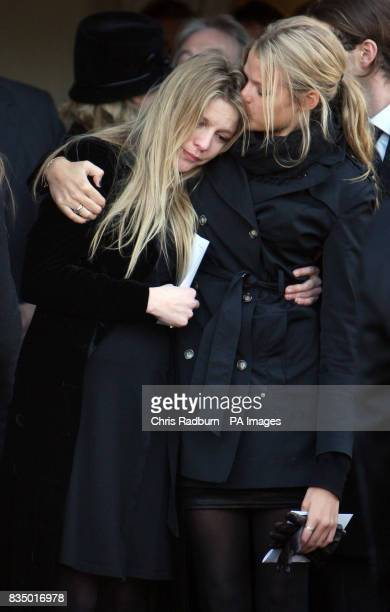Olivia and Arabella the daughters Sir Dai Llewellyn comfort each other at their fathers funeral at St Marys Church Coddenham Suffolk