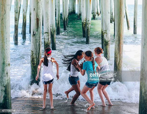 Olivia Coppeta Chadda Chhoeun Maren Harnois and Emily Sawyer all of Westbrook run back from the cold water under the pier in Old Orchard Beach ME on...