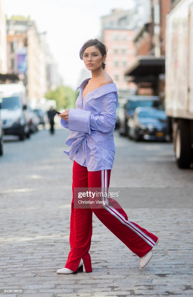 Olivia Culpo is seen wearing a blue white striped button shirt with long sleeves Off White, red pants Anderson bell, white boots Stuart Weitzman, glasses Chloe in the streets of Manhattan during New York Fashion Week on September 7, 2017 in New York City