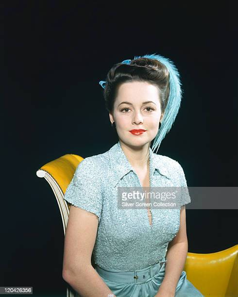 Olivia de Havilland British actress wearing a blue dress with a matching blue feather in her hair sitting on a yellow sofa in a studio portrait...