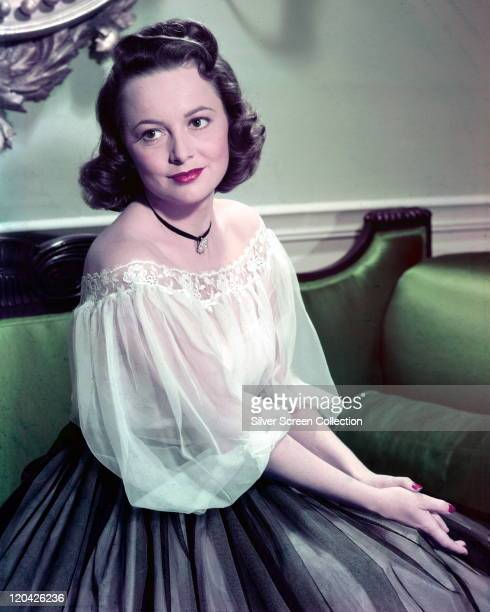 Olivia de Havilland British actress wearing a lacetrimmed white shoulderless top posing in a studio portrait circa 1935