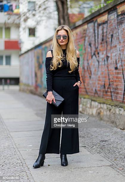 Olivia Faeh wearing a black strapless Cameo Collective top black Sandro pants a black Saint Laurent clutch Dior sunglasses black Alexander Wang boots...