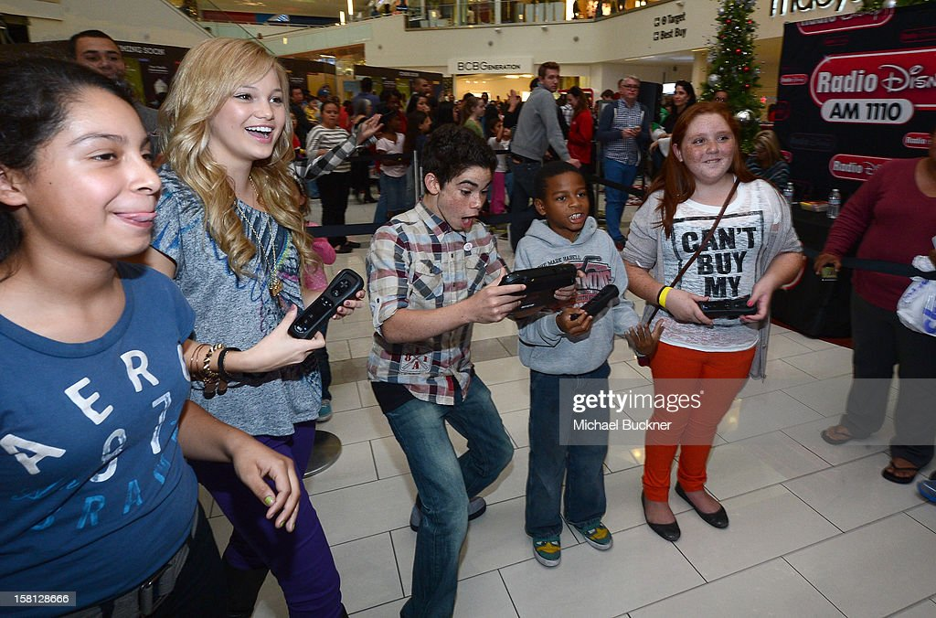 Olivia Holt (L) and Cameron Boyce stars of Disney Channel's hit series 'Jessie' battle in the Wii U Showdown at Westfield Century City Mall in Los Angeles on December 9, 2012. Wii U is one of Nintendo's hottest items of the holiday season.