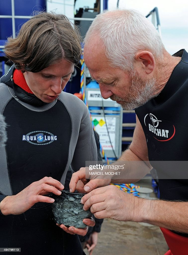 Olivia Hulot (L), of the French Culture Ministry's underwater archaeology department DRASSM (Department des recherches archeologiques subaquatiques et sous-marines) and Jean-Michel Keroulle (R) of the Breton department Morbihan maritime archaeological society SAMM (Societe Archeologie Maritime du Morbihan), look at an item found on the 'Thesee' shipwreck in the Atlantic ocean, off the western French coast, near Quiberon, on May 25, 2014. The ship, carrying 74 guns, sank in 1759 during the Battle of Quiberon Bay, opposing the British and French fleets.