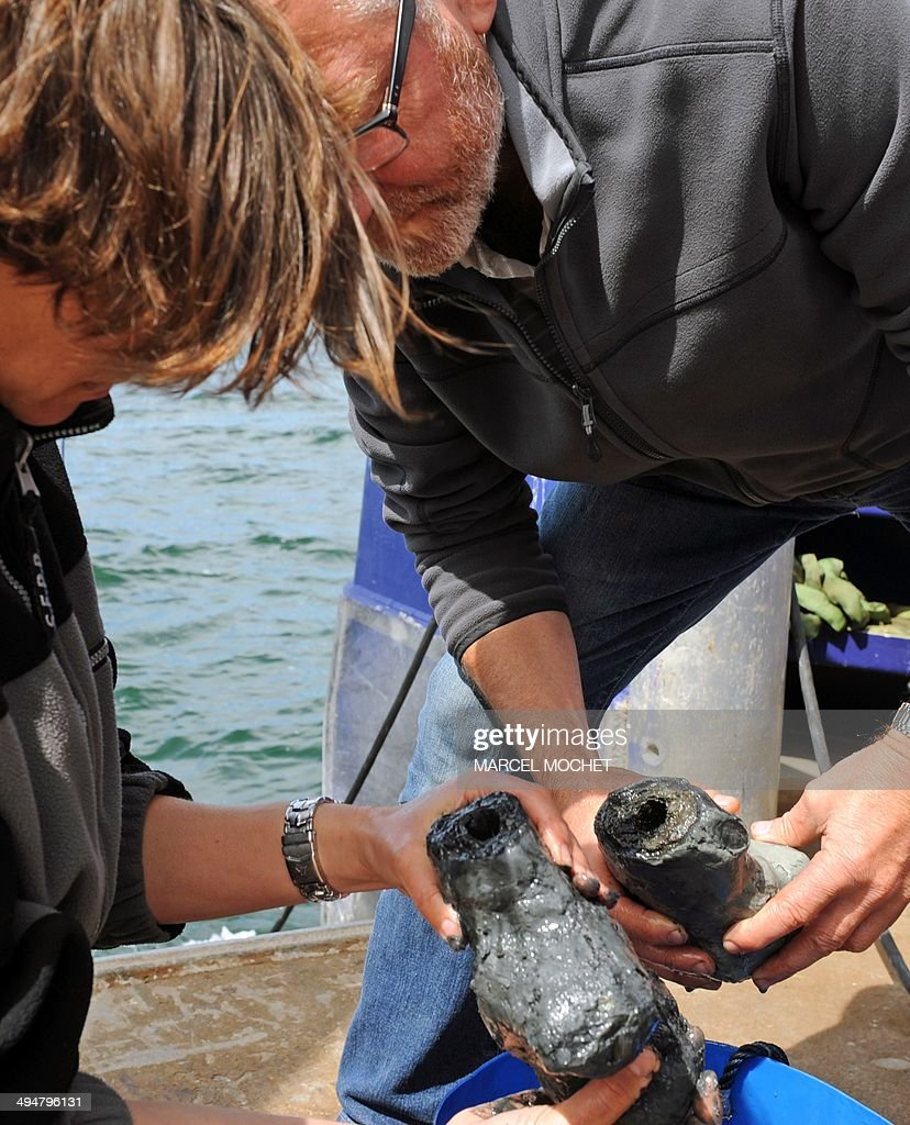 Olivia Hulot (L), of the French Culture Ministry's underwater archaeology department DRASSM (Department des recherches archeologiques subaquatiques et sous-marines) and Jean-Michel Keroulle (R) of the Breton department Morbihan maritime archaeological society SAMM (Societe Archeologie Maritime du Morbihan), look at metal concretions found on the 'Thesee' shipwreck in the Atlantic ocean, off the western French coast, near Quiberon, on May 26, 2014. The ship, carrying 74 guns, sank in 1759 during the Battle of Quiberon Bay, opposing the British and French fleets. AFP PHOTO / MARCEL MOCHET