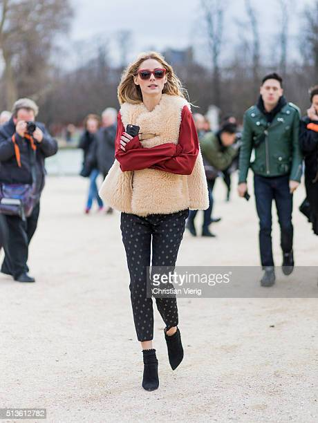 Olivia Palermo wearing a fur vest red jumper and black pants outside Carven during the Paris Fashion Week Womenswear Fall/Winter 2016/2017 on March 3...
